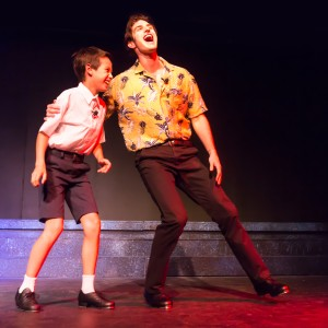 Pictured L to R: Cameron Zener as Young Peter and Justin Genna* as Peter Allen in THE BOY FROM OZ, directed by John Fisher; a Theatre Rhinoceros Production at The Gateway Theatre. Photo by David Wilson.